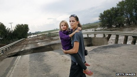 A mother and daughter view a damaged bridge in Longmont, Colorado, on 13 September 2013