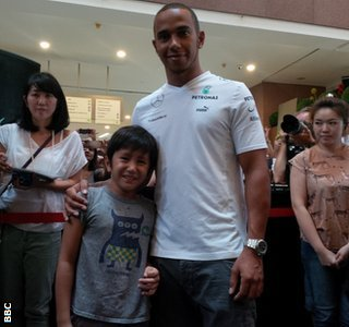 Lewis Hamilton poses with a fan