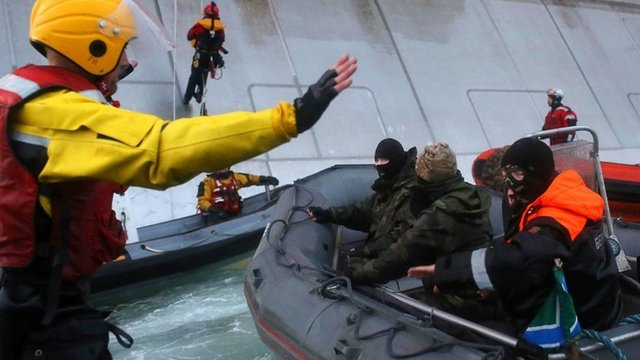 Greenpeace handout photo of Russian coast guard officers in a boat approaching activists