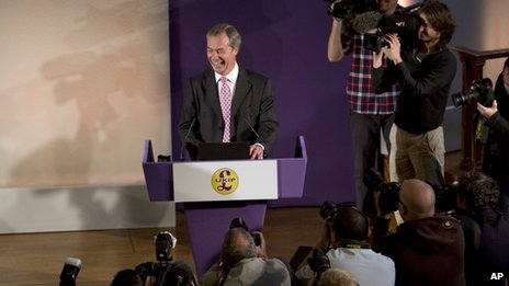 Nigel Farage laughing in front of photographers and TV cameras