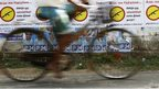 A man cycles past election posters in Jaffna, Sri Lanka, 20 September 2013