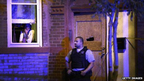 A police officer stands guard outside a home where a man was shot in the chest in the Humboldt Park neighbourhood on the city's Westside in Chicago, Illinois, on 20 September 2013