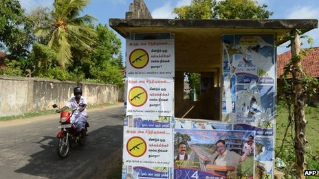 "A Sri Lankan Tamil man cycles past a poster in Jaffna, which says: ""Are you ready to go for another war?"""