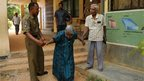 A Sri Lankan Police officer helps an elderly ethnic Tamil couple