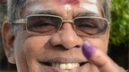 A Sri Lankan man holds up his inked finger after voting at a polling station in Jaffna