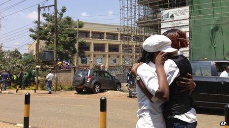 Two women hug outside an upscale shopping mall, seen background left , in Nairobi, Kenya Saturday 21 September 2013.