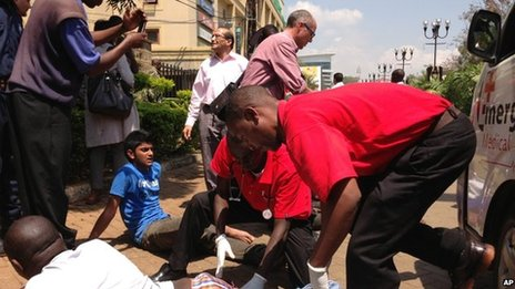 An injured man is treated outside an upmarket shopping mall, seen background, in Nairobi, Kenya, 21 September 2013.