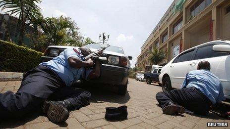 Police take cover outside Westgate shopping centre where gunmen went on a shooting spree in Nairobi on 21 September 2013.