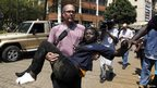 A journalist rescues a woman injured in a shootout between armed men and the police at the Westgate shopping mall in Nairobi 21 September, 2013.