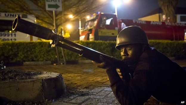 An armed police officer takes cover during a bout of gunfire outside the Westgate Mall