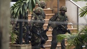 Soldiers from the Kenya Defence Forces carry a wounded colleague, following the sound of explosions and gunfire, out of the Westgate Mall in Nairobi, Kenya Sunday, 22 September, 2013.