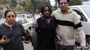 A woman is escorted after being evacuated from the Westgate shopping mall in Nairobi 22 September, 2013.