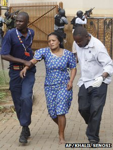 A woman is led to safety by security guards