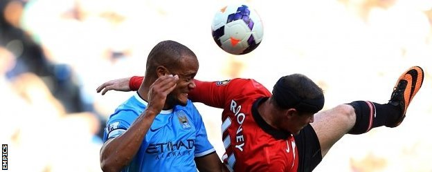 Vincent Kompany battles for the ball with Manchester United striker Wayne Rooney
