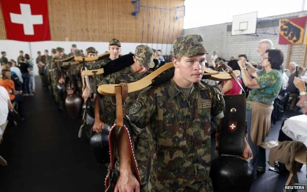 Recruits from the veterinary troops of the Swiss Army play traditional cow-bells during an official visiting day at a Swiss army base in Sand bei Schoehnbuehl, outside Bern 7 September, 2013.