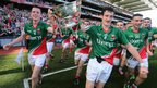 Mayo captain Stephen Coen and Val Roughneen hold the Tommy Markham Cup aloft after their victory over the Red Hands