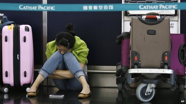 A passenger waits for flights to resume while sitting an airline counter at Hong Kong's international airport after Typhoon Usagi slammed into southern China, Monday, 23 September 2013
