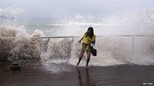 A woman reacts as a storm surge past a barrier on the shore as Typhoon Usagi approaches Shenzhen, Guangdong province, 22 September 2013