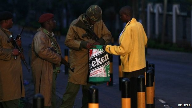 Kenyan policemen search a man as he walks past the Westgate Shopping Centre