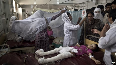 Pakistani girl who was injured in a suicide attack on a church lies in a hospital bed surrounded by relatives and nurses