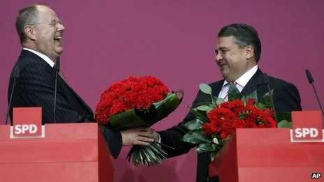 SPD candidate Peer Steinbrueck is given a bunch of flowers by the party's chairman, Sigmar Gabriel