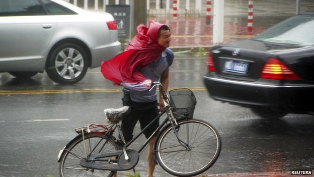A man pushes his bicycle against the wind as Typhoon Usagi approaches Shantou, Guangdong province, 22 September 2013