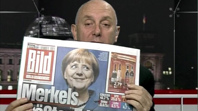 Steve Evans holds German newspaper