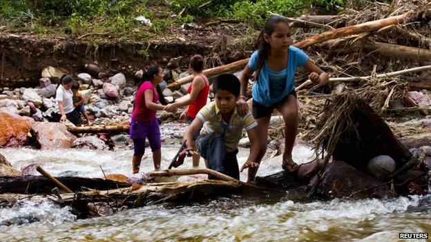 Children cross a river on the mountain range of Zihuatanejo in Guerrero state on 22 September, 2013
