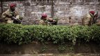 Kenya security forces are seen behind a wall outside the Westgate Mall in Nairobi