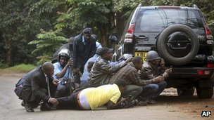Kenyan security personnel and journalists duck behind a vehicle