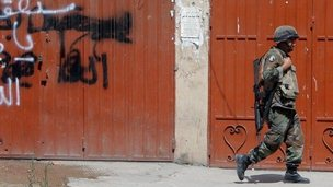 A Lebanese army soldier walks past graffiti on a closed shop in Tripoli