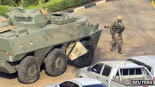 A Kenya Defence Forces soldier carrying a rocket-propelled grenade (RPG) walks past an armoured military vehicle in front of the Westgate shopping centre (23 September 2013)