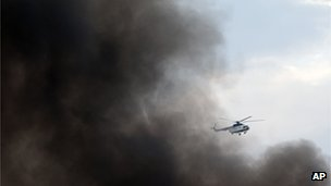 A Kenyan Army helicopter flies through the plume of black smoke over the Westgate Mall, in Nairobi, Kenya (23 Sept. 2013)