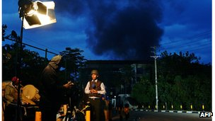 A Kenyan TV presenter stands in front of smoke rising from Westgate Mall on September 23, 2013