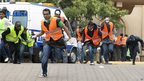Kenyan Terror Attack: Paramedics run for cover on September 23, 2013 outside the Westgate Mall in Nairobi after heavy shooting started.