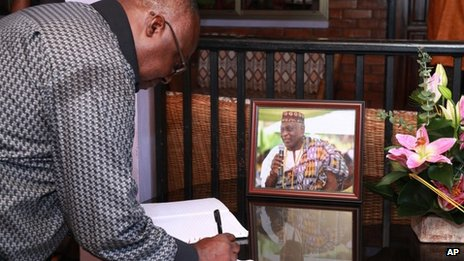 A mourner signs condolences book for Ghanaian poet, professor, and former ambassador Kofi Awoonor, seen in the framed photograph, at his residence in Accra, Ghana, Monday, 23 September 2013