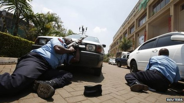 Police take cover outside Westgate shopping centre where gunmen went on a shooting spree in Nairobi on 21 September 2013.