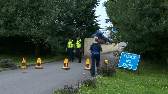 Police at the entrance to the farm