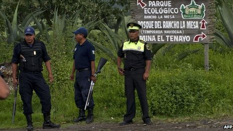 Security forces guard the entrance to a ranch where 13 bodies were found in August 2013