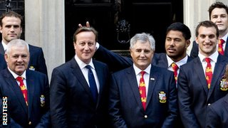 England centre Manu Tuilagi makes a gesture behind Britain's Prime Minister David Cameron (centre), as he poses with the British and Irish Lions rugby squad