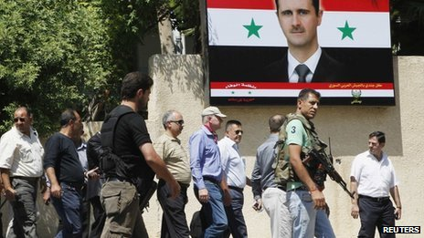 Ake Sellstrom and his team in Syria, walking past a poster of Bashar al-Assad, August 2013