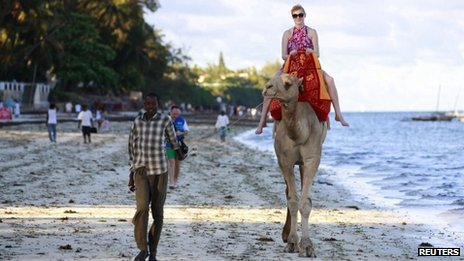 A tourist rides on a camel's back at the Jomo Kenyatta public beach in Kenya's coastal city of Mombasa, March 24, 2013