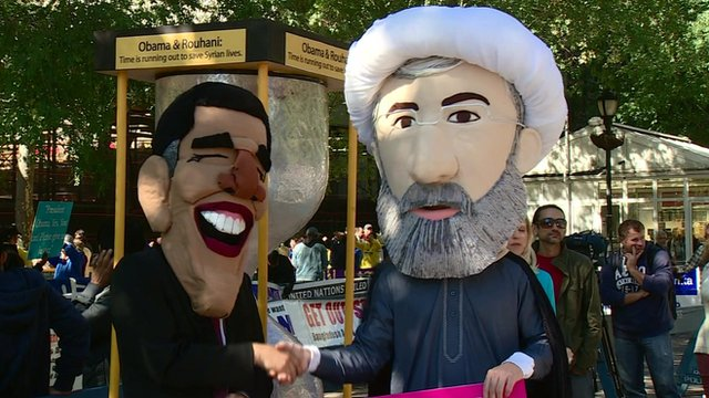 Men wearing masks of Presidents Obama and Rouhani, shaking hands