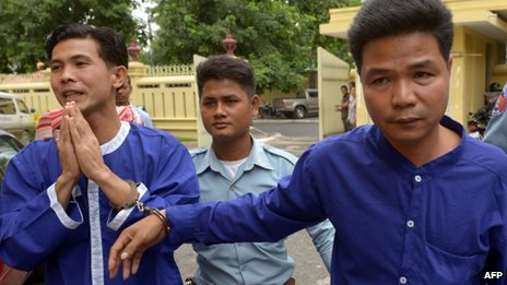 Born Samnang (left) and Sok Sam Oeun (right), are escorted by a prison guard to the supreme court in Phnom Penh on 25 September 2013