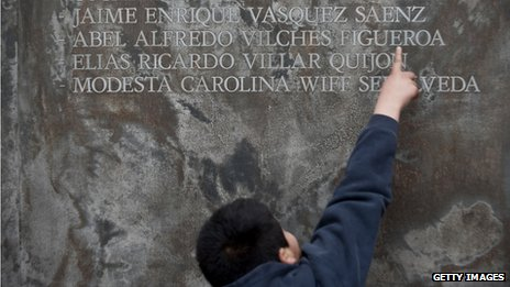 A child points to names on a memorial honouring those killed or disappeared under military rule in Chile on 11 September 2013