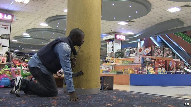 A member of the security team holds a gun as he hides behind a pillar