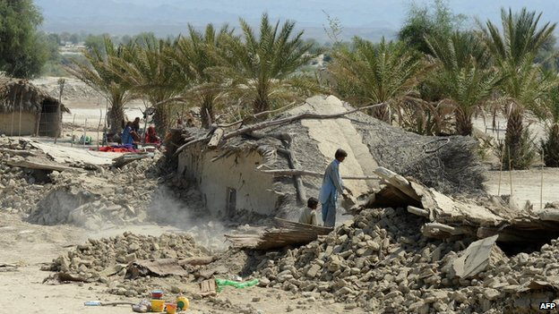 Pakistani survivors remove the debris of their destroyed houses
