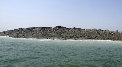 People walk on an island that reportedly emerged off the Gwadar coastline in the Arabian Sea