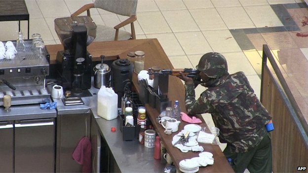 A soldier aims his gun while he leans on a coffee bar