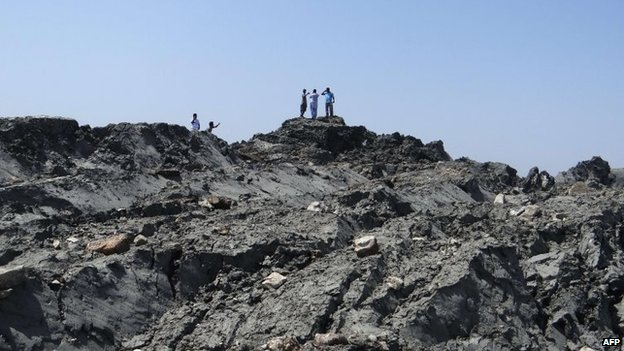 In this photo released by the Pakistani Government, Pakistani men walk on an island that appeared two kilometres off the coastline of Gwadar on 25 September, 2013, after an earthquake.